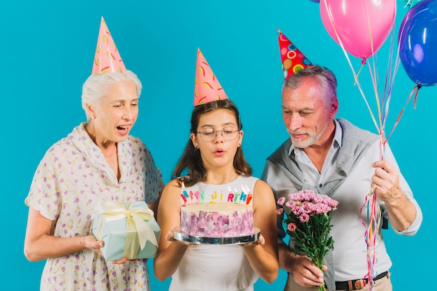 Grandparents holding birthday gifts near girl with cake blowing candles on blue backdrop