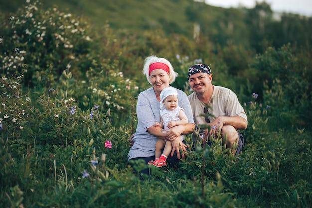 공원 자연에 앉아 손녀를 들고 조부모