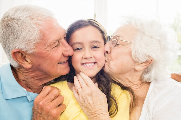 Grandparents kissing their granddaughter at home