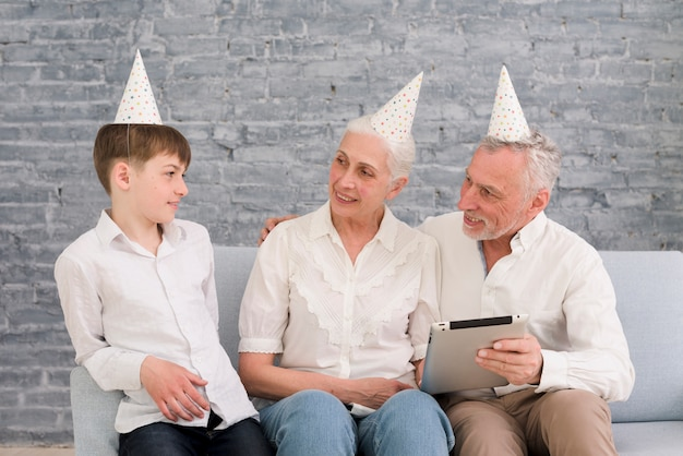 Бабушка и дедушка смотрят на своего внука, держа в руке цифровой планшет