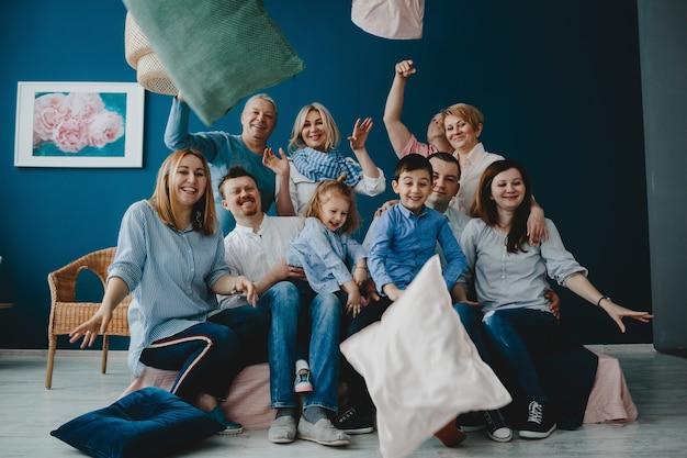 Бабушки и дедушки, родители и их маленькие дети сидят вместе на кровати в синей комнате