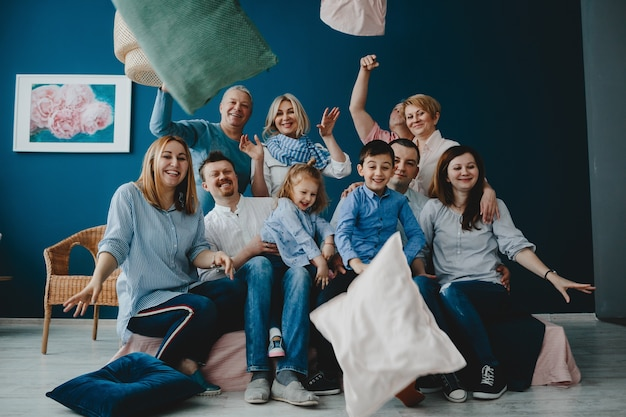 Grandparents, parents and their little children sit together on the bed in a blue room