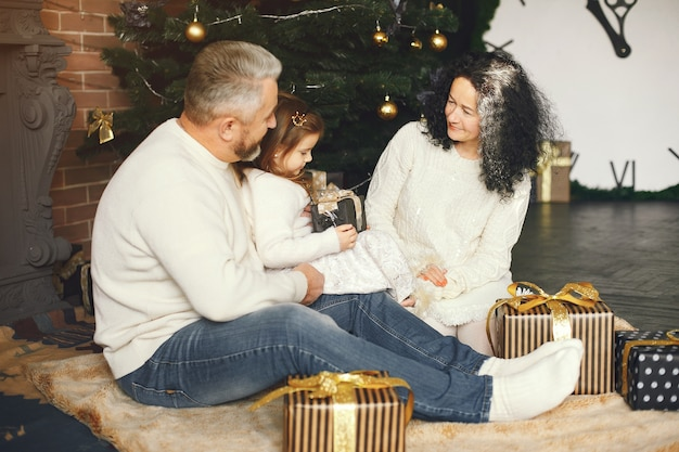 Grandparents sitting with their granddaughter. celebrating christmas in a cozy house.