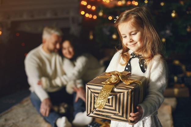 孫娘と一緒に座っている祖父母。居心地の良い家でクリスマスを祝います。