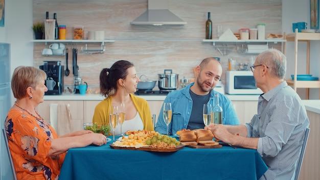 リラックスした家族の日を過ごす祖父母。多世代、4人、2人の幸せなカップルがグルメディナーの最中に話したり食事をしたり、家での時間を楽しんだりします。