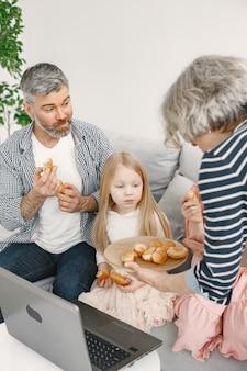 孫と過ごす祖父母。女の子におやつをあげるおばあちゃん。彼らはソファに座って、ラップトップをテーブルに置いています。