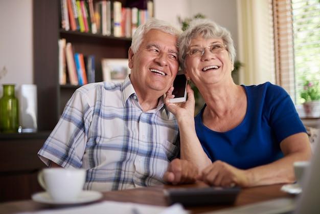 테이블에서 전화 통화하는 조부모