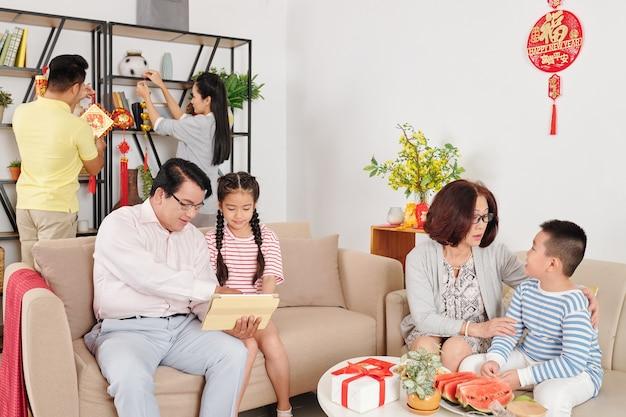 Бабушка и дедушка разговаривают с внуками, когда родители украшают гостиную для празднования китайского нового года