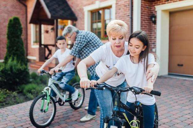 Бабушка и дедушка учат внучку и внука кататься на велосипеде.