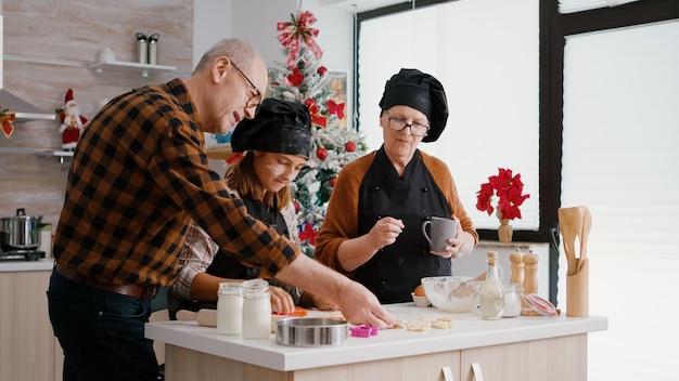 Бабушка и дедушка учат внучку делать рождественские домашние пряники