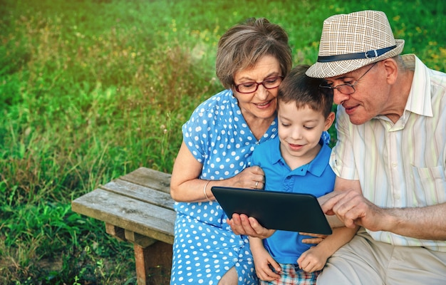 Бабушка и дедушка с помощью планшета с внуком, сидя на скамейке на открытом воздухе
