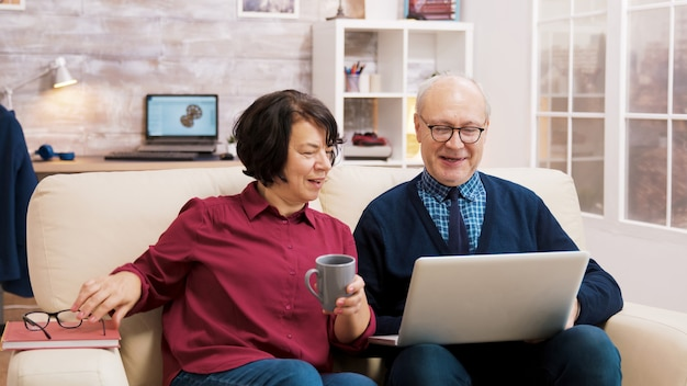 Grandparents with glasses sitting on sofa talking with family during a video call on laptop.