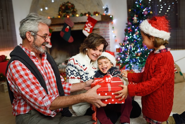 Grandparents with grandchildren opening gift boxes