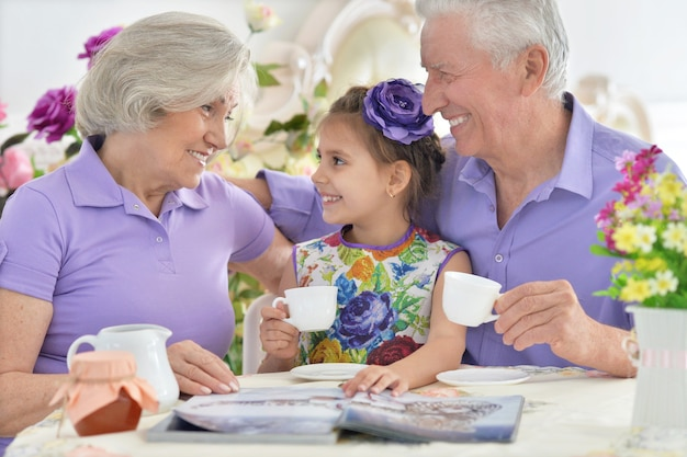 Grandparents with granddaughter drinking tea and reading magazine
