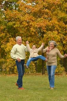秋の公園で楽しんでいる孫娘と祖父母