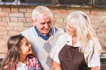 Grandparents with granddaughter in kitchen