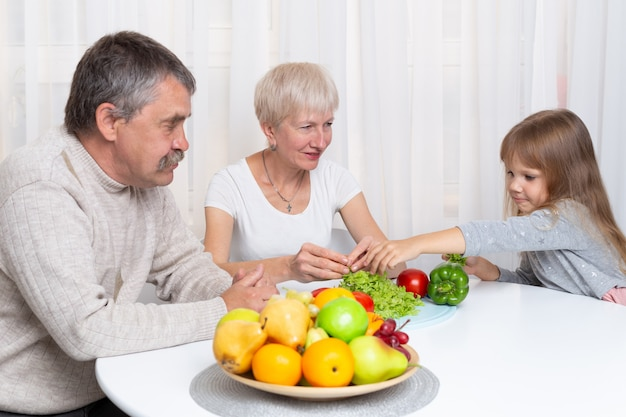 Grandparents with granddaughter prepare healthy food in the kitchen. family preparing a salad together