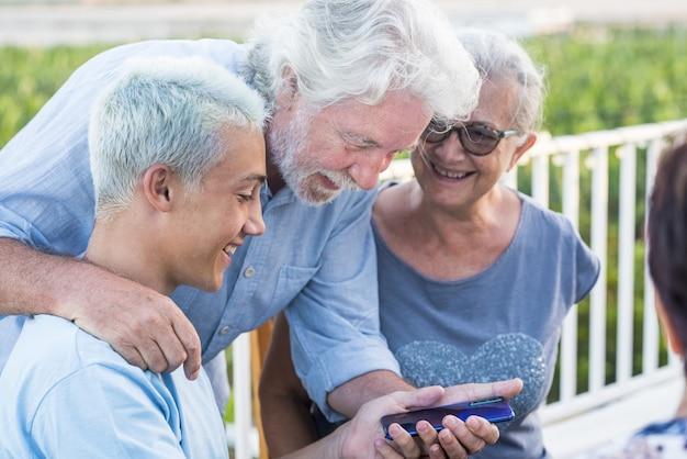 携帯電話を見ている孫を持つ祖父母。携帯電話デバイスの背面を見て幸せな多世代家族。