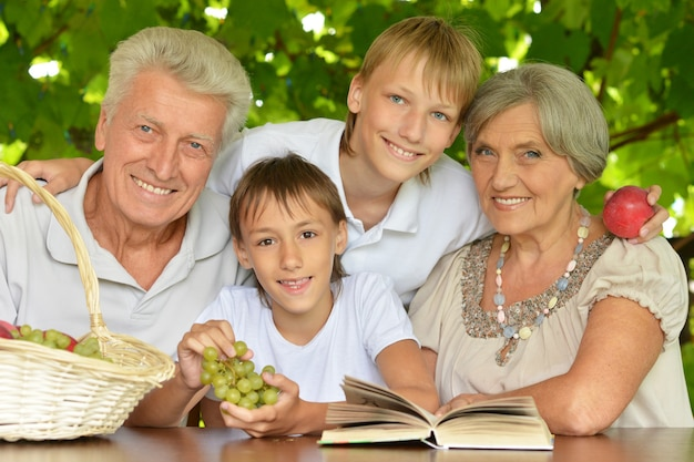 Grandparents with grandsons reading in summer at tablereading in summer at table