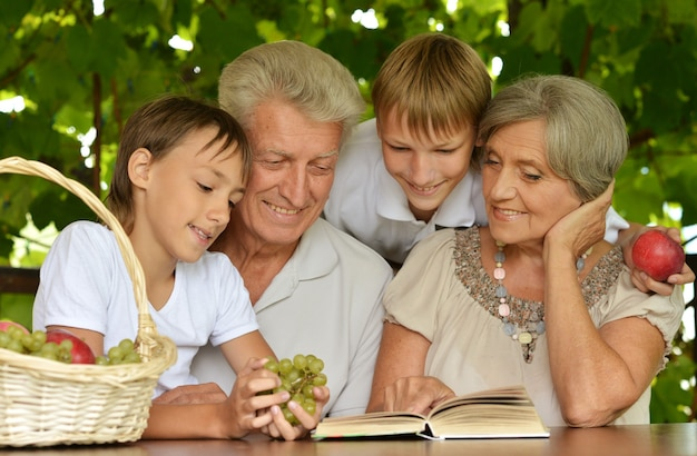 Grandparents with her grandson reading in summer at table