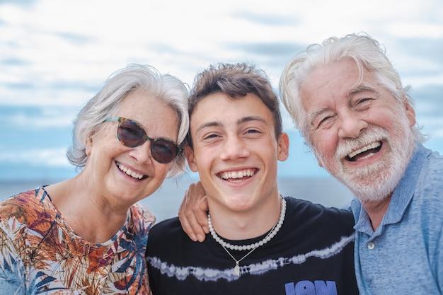 10대 소년 손자와 함께 조부모는 바다에서 서로 껴안고 즐겁게 웃고 있습니다.
