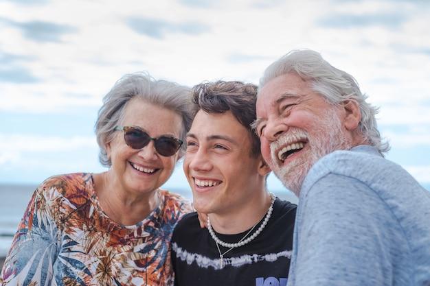 10대 손자와 함께 바다에서 서로 껴안고 즐거운 시간을 보내고 웃고 있는 조부모