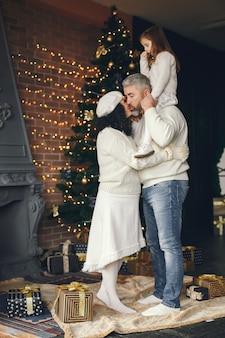 祖父母と孫娘。居心地の良い家でクリスマスを祝います。