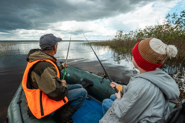 Внук и дедушка вместе рыбачат с лодки на озере.