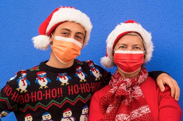 サンタの帽子をかぶった孫と祖母は、コロナウイルスcovid-19のためにサージカルマスクを着用してカメラを見ています。青い壁の背景。家族、友情、ニューノーマルの概念