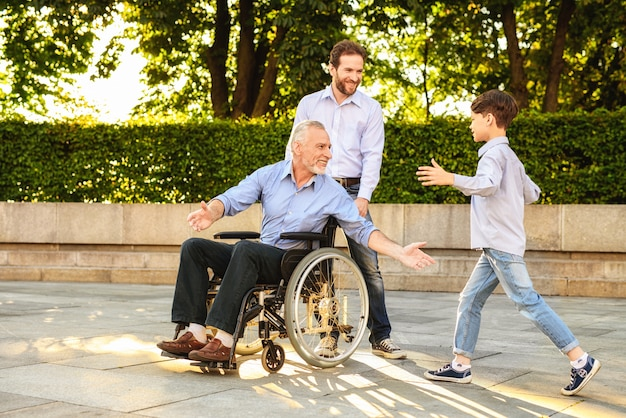 Grandson come to pensioner sit in wheelchair.