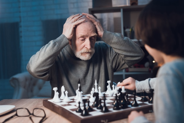 Grandson and grandfather playing chess together