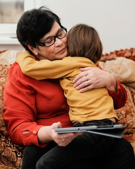 Grandson hugging his grandmother while she holds a tablet