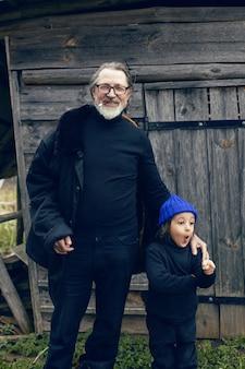 파란색 모자를 쓴 손자와 양가죽 코트를 입은 할아버지가 있는 부츠는 러시아 봄에 마을에 있는 목조 가옥에 서 있다