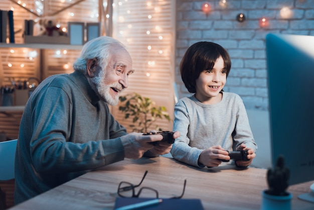 Grandson playing video games with grandfather