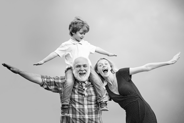 손자는 할아버지의 어깨에 앉습니다. 할아버지와 함께 재미있는 시간. 늙은이와 젊은이