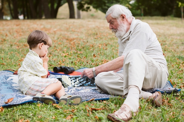 Grandson with grandpa in park at picnic