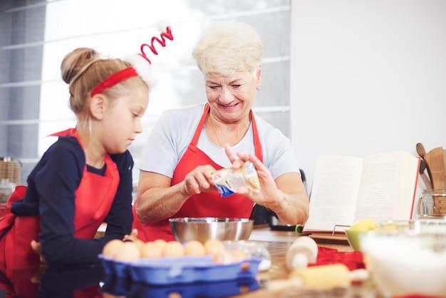 孫娘に自家製のお菓子を作るように教えるおばあさん