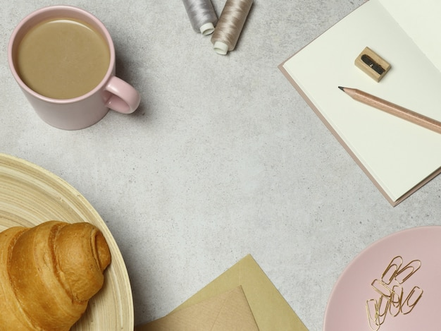 Granite background with pink cup of coffee and  croissant, notes, envelope, clips