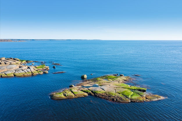 Granite island with green moss in the sea. top view.