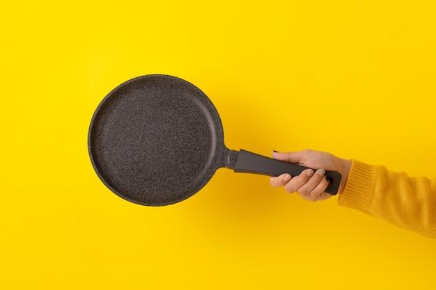 黄色の上に手にパンケーキのための花崗岩の鍋