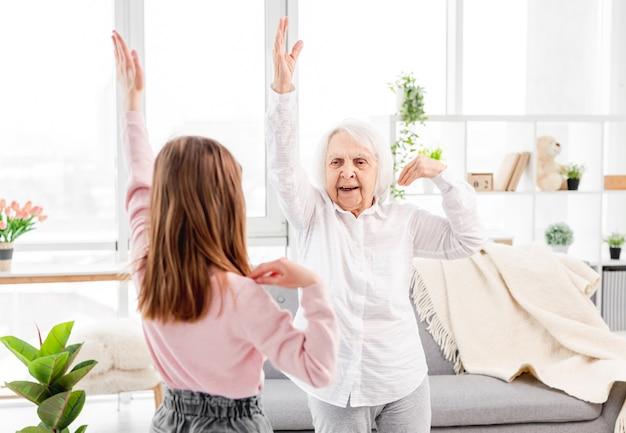 Бабушка и внучка вместе делают упражнения для плеч и спины дома