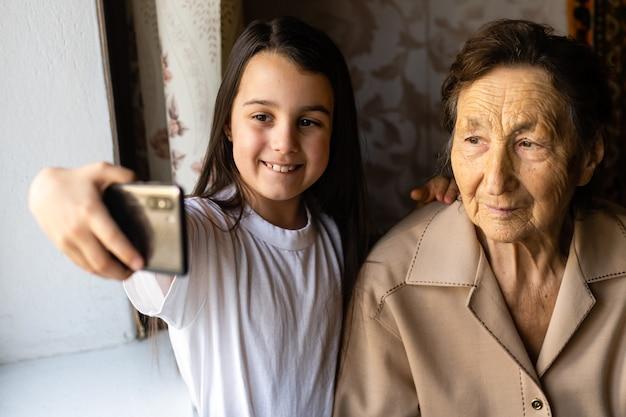 Бабушка и внучка. милая маленькая девочка показывает бабушке смартфон.