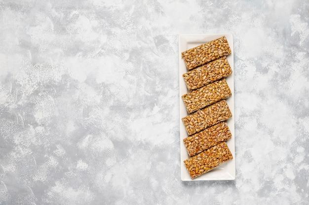 Granola bar. healthy sweet dessert snack. sesame, peanut, sunflower in honey. gozinaki is georgian national food, oriental sweet. top view on concrete