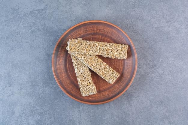 Батончики мюсли в деревянной тарелке, на мраморной поверхности