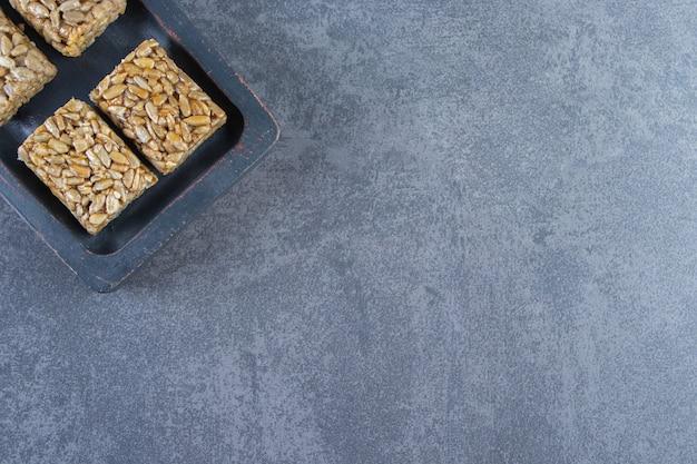 Батончики мюсли в деревянной тарелке на мраморной поверхности