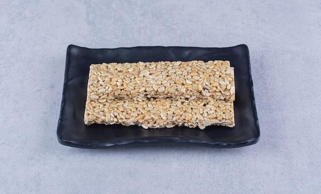 Батончики мюсли на блюде на мраморной поверхности