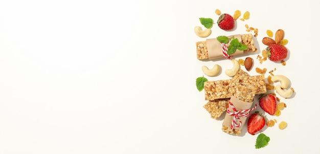 Батончики мюсли, клубника и орехи на белом фоне, место для текста