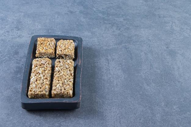 Barrette di muesli in un piatto di legno, sullo sfondo di marmo.
