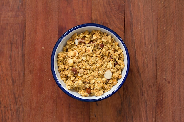 Granola in bowl on brown wooden surface