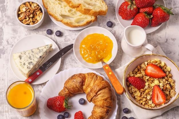 Granola, bread, cheese, jam, juice for healthy breakfast.